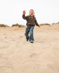 boy running down a sand dune