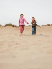 children running down a sand dune