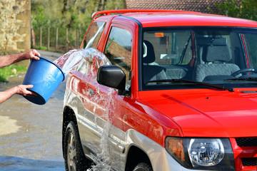 lavando y aclarando un coche rojo con cubos de agua