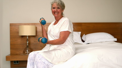 Senior woman lifting dumbbells in bedroom
