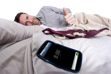 alarm clock on a digital cell phone display with man in bed