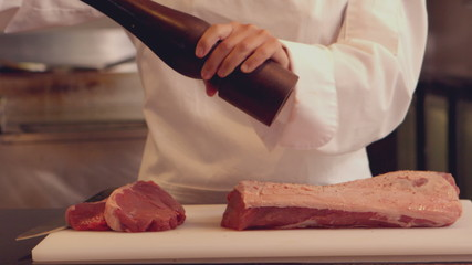Chef seasoning a piece of beef