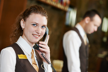 Hotel worker with phone on reception