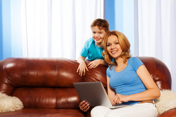 Smiling mother with laptop and her son together