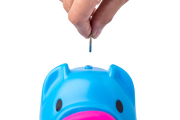 Saving, female hand putting a coin into piggy bank.