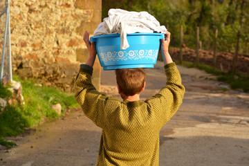 mujer mayor lavandera con cubo con ropa en la cabeza