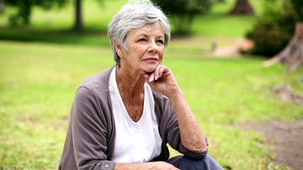 Upset senior woman sitting in the park thinking