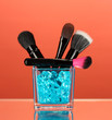 Make-up brushes in glass cup with stones on red background