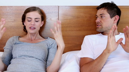 Unhappy couple arguing on bed