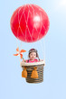 cheerful kid on hot air balloon in the sky