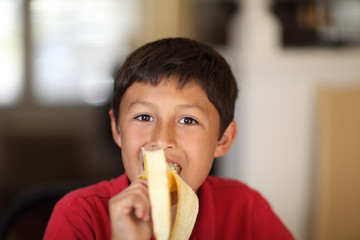 Young boy eating a banana