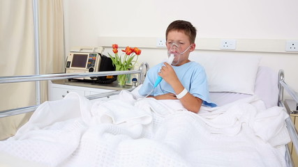 Little sick boy sitting in bed with oxygen mask