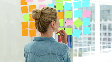 Blonde designer looking at post its on window