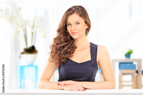 Beautiful woman posing at a table indoors