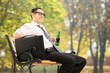 Man holding a beer and relaxing in park