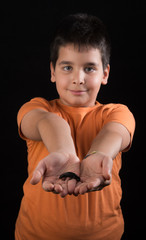 Little boy holding a small newt on black background
