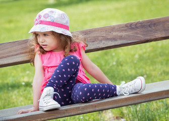 Cute little girl sitting on the bench in a park