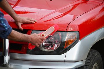 limpiando luces de un coche rojo con un cepillo