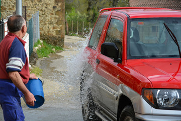 hombre mayor lanzando agua para aclarar un coche rojo