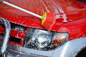 lavando coche rojo con agua y jabon