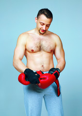 Fit man putting his boxing gloves, preparing for training