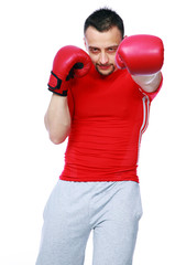 Fitness man punching with red boxing gloves