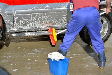 hombre limpiando un coche con un cepillo, agua y jabon