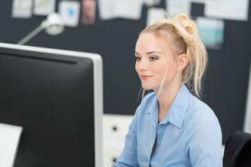 junge frau arbeitet im büro am pc