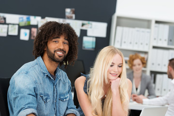 lächelnder junger mann mit kollegen im büro