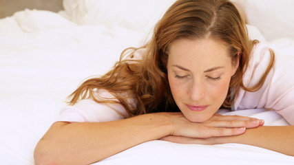 Peaceful woman lying in bed smiling up at camera