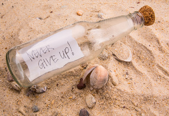 Concept image of a message NEVER GIVE UP in a bottle