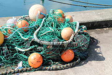A Fishing Net with Floats on a Quayside Wall.
