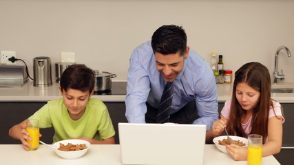 Smiling father using laptop with children before he goes to work