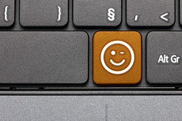 Wink. Orange hot key emoticon on computer keyboard.