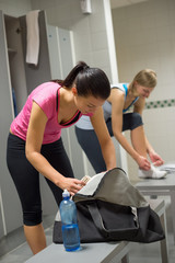 Woman packing bag at gym's locker room