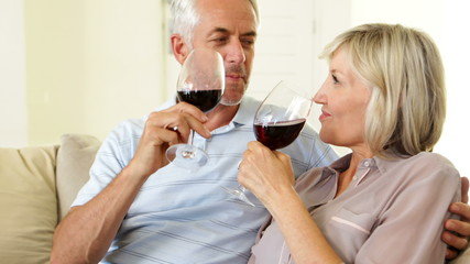 Couple relaxing together on the couch drinking red wine