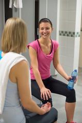 Woman smiling at friend in locker room