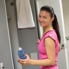 Woman holding bottle at gym's locker room