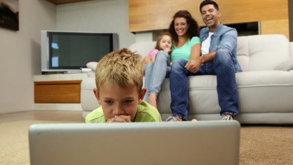 Little boy lying on floor using laptop with family behind him on