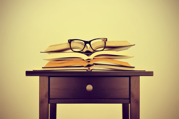 books and eyeglasses on a desk, with a retro effect