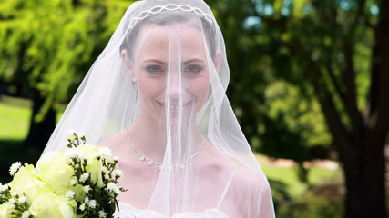Pretty bride smiling at camera with veil over her face