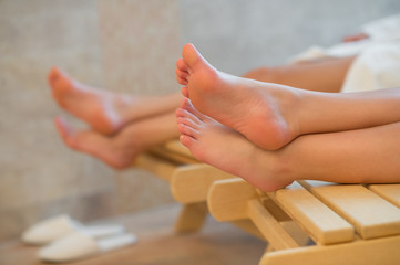 Feet of two women relaxing spa room