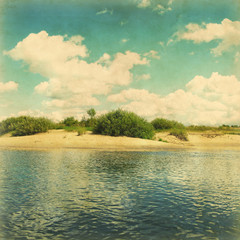 Coast of river under blue sky with clouds in grunge and retro st