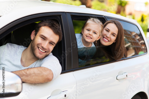 Family sitting in the car looking out windows - 64718583