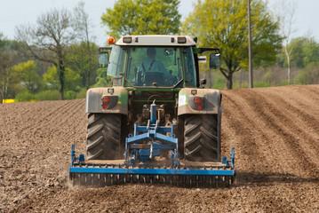 Traktor mit Kreiselegge bei der Feldbearbeitung  - 1524