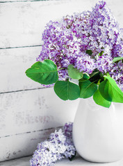 Lilacs in white vase on rustic background