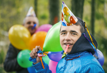 Boy with balloons in birthday party at outdoors