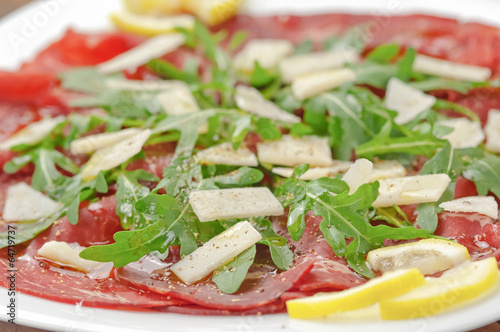 Closeup bresaola with arugula salad and olive oil