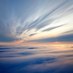 Flight between clouds during sunrise