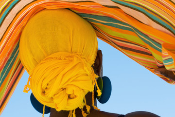 African woman with colorful head scarf
